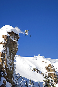 A male skier jumps off a 100 foot cliff known as the diving board in the Grand Targhee Backcountry, Wyoming.