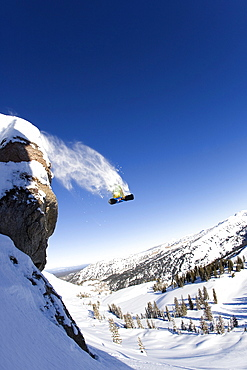 A male snowboarder jumps off a large cliff in the Grand Targhee ski area backcountry, Wyoming.