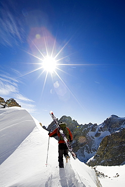A male skier climbs a ridge near the top Garnet Canyon towards during a stellar day of touring in the Grand Teton National Park, Wyoming.
