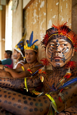 An Oro Win man painted as a jaguar and other members of the community relax after a large feast during a traditional