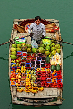 fruit seller paddles boxes of fruit in a boat on Halong Bay.