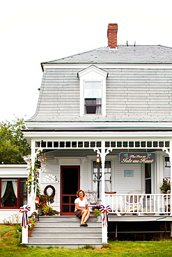 A innkeeper sits on the porch of her bed & breakfast.