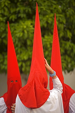 Penitent walk in a street during Easter Holy Week celebrations in Carmona village, Seville province, Andalusia, Spain.