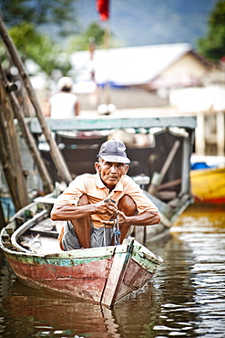 A man peers out from his small fishing boat near the dock in Sukadana, Indonesian Borneo.