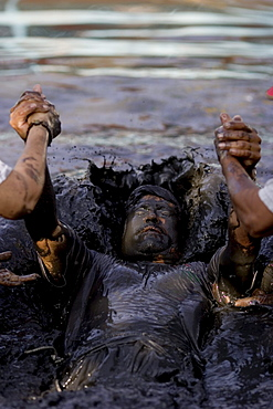 A man is baptized in the healing mud of Espinoza, Mexico.Twice a year the faithful visit Espinazo, a small dusty village and birthplace of El Nino Fidencio, one of the most revered healers in North East Mexico.  Although he died in the 1940s people believe certain priests known as Materias can channel his healing gifts and cure people.  During the anniversary of his birth and death over 100,000 people take part in the celebration by giving thanks at his gravesite or bathing and getting healed in mud baths.
