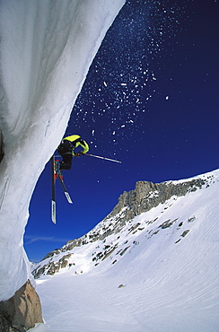 A skier hucks off of a cliff while backcounrty skiing near Tuolumne Meadows, California.