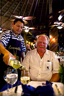 A waiter pours white wine for a guest at a restaurant in Cancun, Mexico.