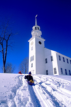 A boy sledding on a snowy hillside in front of the church in Strafford, Vermont on a clear, cold winter day.