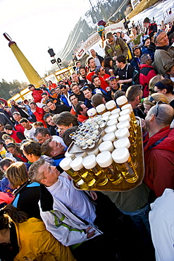 A waiter carries thirty nine and half liters of beer and a tray of shots through a crowd at the Mooserwirt apres-ski ar in St. Anton am Arlberg, Austria.