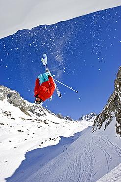 A man performs a back flip off a cornice while skiing off-piste near St. Anton am Arleberg, Austria.