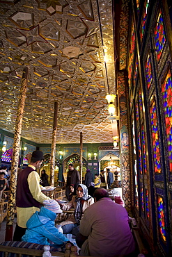 Esfahan, Iran - February, 2008: Iranian family having lunch in a colorful traditional looking restaurant on Imam Square in Esfahan, Iran.