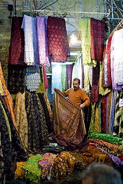 Shiraz, Iran - February, 2008: Silk salesman inside the colorful bazaar in Shiraz, Iran.