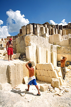 Men work at a limestone cooperative quarry, just outside the city of Matanzas, Cuba. The stone is cut with long-toothed handsaws, and carried through the quarry to a waiting truck.