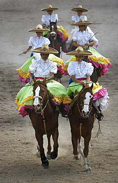 """Members of the El Herradero team compete in an Escaramuza in Mexico City, Sunday, February 10, 2008.  Escaramuzas are similar to US rodeos, where female competitors called """"Amazonas"""" wear long skirts, and ride side saddle.  Male rodeo competitors are """"Charros,"""" from which comes the word """"Charreria."""" Charreria is Mexico's national sport."""