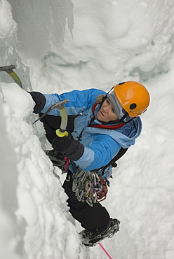 A professional female climber ice climbing a frozen waterfall in Colorado.