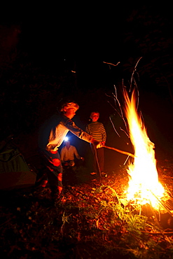 Two boys roast marshmallows over a campfire.