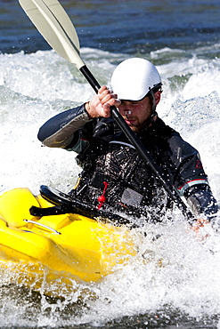 A male kayaker in a playboat paddles on the Clark Fork River, Missoula, Montana.