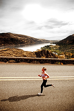 An athletic woman jogging along a deserted road on a beautiful fall day with the Columbia River Gorge in the distance.