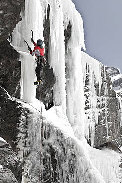 A woman ice climbing up a frozen waterfall at Willow Lake in the Sangre De Cristo Mountains, Crestone, Colorado.