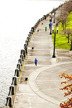 An athletic female in a blue jacket jogging near the Portland, Oregon waterfront.