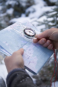 A male hiker checks his location with a compass and topographic map.