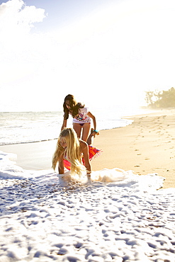 Two pre-teen girls play at Paia Beach, Maui, Hawaii and laugh as the wave gets them wet.