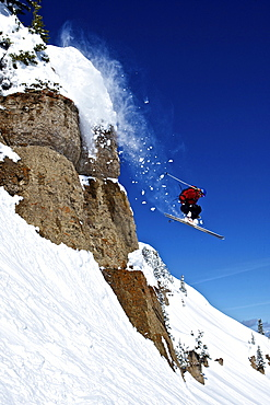 A man skis off a cliff in Wyoming.