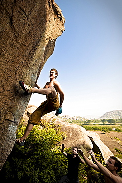Topless caucasian male chalking up mid-climb on a boulder in Hampi, India.