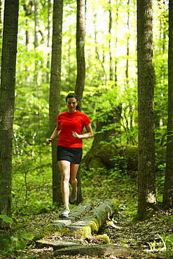 Woman trail running in a lush green forest.