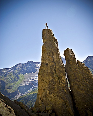 A rock climber stands on top of a pinnacle that he just completed in  the French Alps.