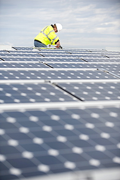 Green energy technician adjusts photovoltaic panels on a roof