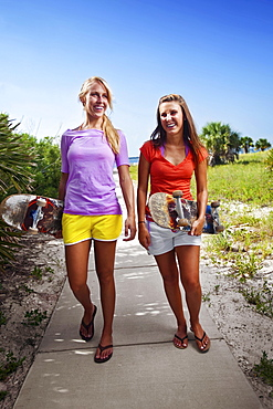 Two girls laughing as they walk with their skateboards on a sidewalk connecting the Santa Rosa Sound with the Gulf of Mexico.