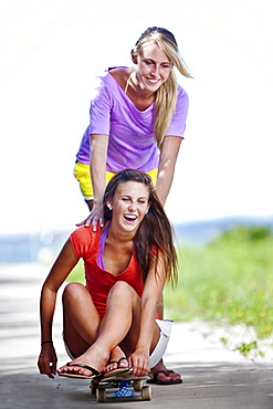 Two girls skateboard on a sidewalk connecting the Santa Rosa Sound with the Gulf of Mexico.