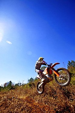A motorcyclist catches air on a jump during an Enduro race in Maplesville, Alabama. (Back lit, Lens Flare, Motion Blur)