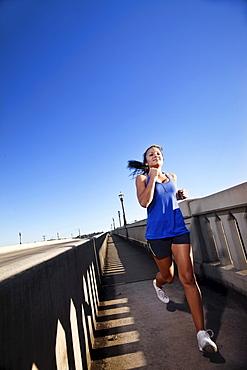 A teenage girl runs downhill on the sidewalk of a bridge in downtown Birmingham, Alabama.