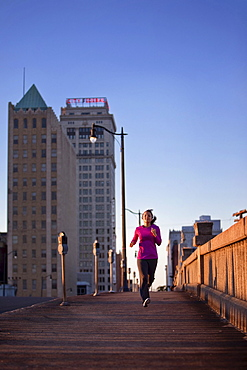A teenage girl runs on a sidewalk at dusk in downtown Birmingham, Alabama with tall buildings in the background (hard lighting)