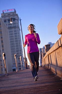 A teenage girl runs on a sidewalk at dusk in downtown Birmingham, Alabama.
