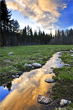 Dramatic clouds at sunset are reflected in a mountain stream creating a surreal effect in Lake Tahoe, CA.