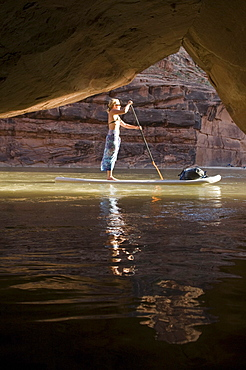 Woman on paddle board in front of cave while rafting down the Lower San Juan River, Mexican Hat, Colorado.