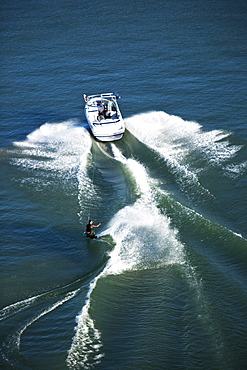 A athletic wakeboarder carves and slashes on a calm day in Idaho. Shot from above.