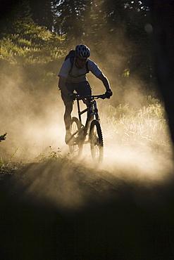 A man mountain biking in the dust.
