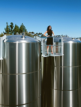 A beautiful lady stands on top of brewery plant in San Diego.
