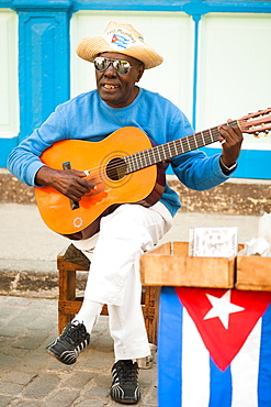 A street musician in Havana, Cuba sings and sells CDs of his music.