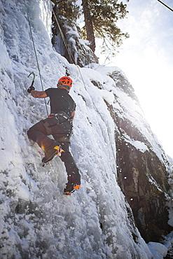 A man climbs a frozen waterfall in Whistler, British Columbia, Canada, Whistler, British Columbia, Canada