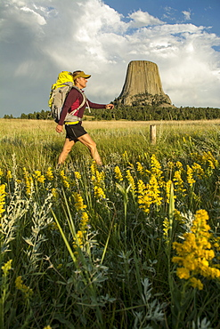 A woman hiking with her backpack below Devil's Tower in Devil's Tower National Monument, Wyoming, Devils Tower, Wyoming, usa