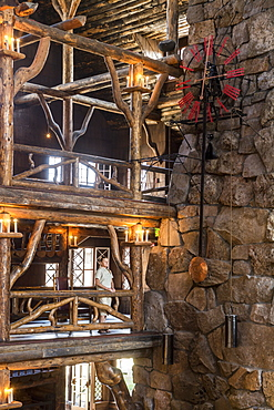 A woman standing next to the intricate log work inside the Old Faithful Lodge in Yellowstone National Park, Wyoming, Yellowstone, Wyoming, usa