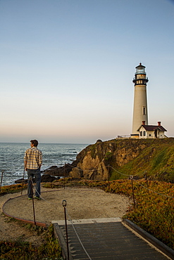 A man enjoys the dusk views at the Pigeon Point Lighthouse near Pescadero, California on a sunny day, Pescadero, California, USA