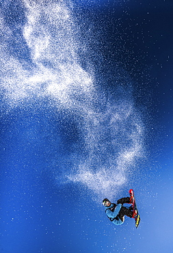 A snowboarder leaping into the air on the Dachstein-Glacier in Austria, leaving a trail of snow behind him.