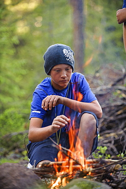 A boy builds a fire in preparation to spend the night out and earn the WIlderness Survival Merit Badge, at the end of Troop 693's six day backpack trip through the High Uintas Wilderness Area, Uintas Range, Utah