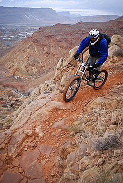 Experienced riders descend a downhill mountain bike trial which drops into the town of Moab, Utah.